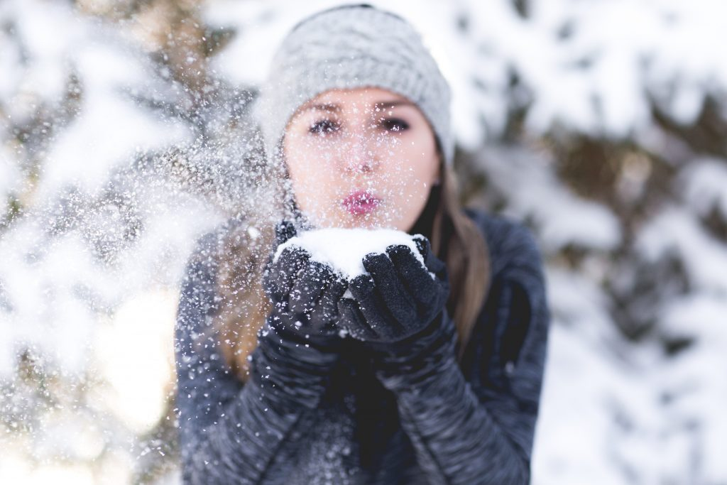lady blowing snow from her hands