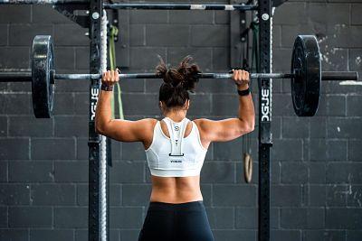 girl using bar bell weights